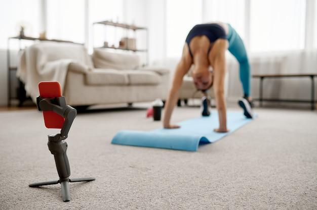 Худенькая девушка делает упражнения на растяжку дома, онлайн-тренировка на ноутбуке
