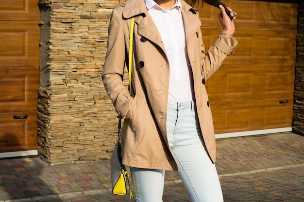 ベージュのコート、ブルージーンズ、屋外の白いシャツでスリムな女の子