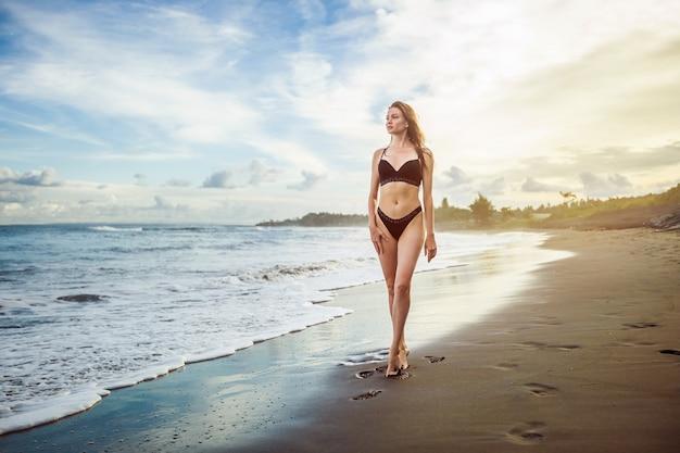 Худенькая девушка в черном купальнике стоит на пляже на фоне красивого заката