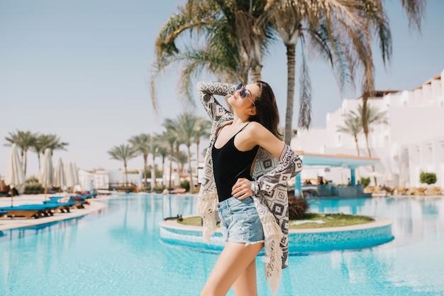 ヤシの木のある屋外プールの近くで優雅にポーズをとるbalckタンクトップのスリムな女の子。エキゾチックなリゾートの夏休みに外で休んで暗いストレートの髪を持つ素敵な若い女性