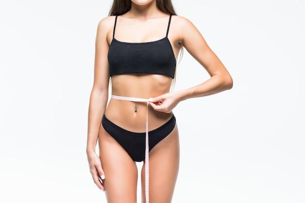 Стройная девушка в черном нижнем белье с мерной лентой на талии. фото красивая брюнетка девушка с идеальным телом. фитнес или концепция ухода за телом