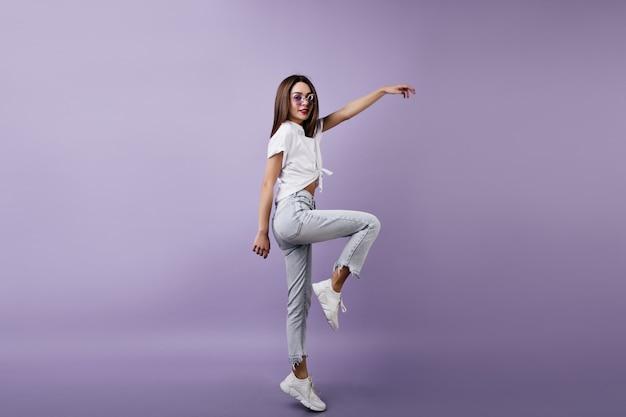 Худенькая девушка в милых белых кроссовках позирует на одной ноге. внутреннее фото мечтательной женщины в танцах джинсов.
