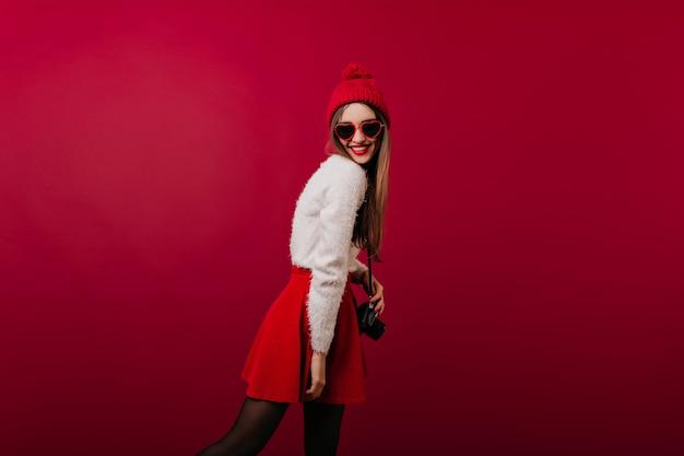 Худенькая девушка в вязаной шапке позирует с камерой и улыбается