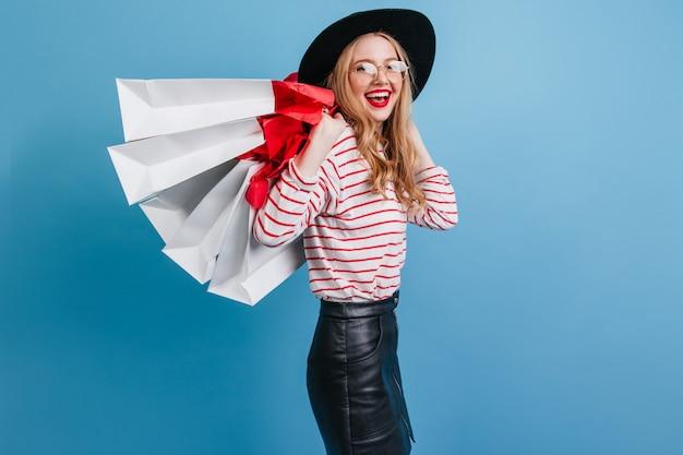 青い背景で笑っている革のスカートのスリムな女の子。ショッピングバッグを持つ金髪の白人女性のスタジオショット。