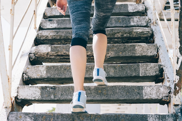 スリムな女の子のスニーカーとスポーツウェアの階段を登るクローズアップ