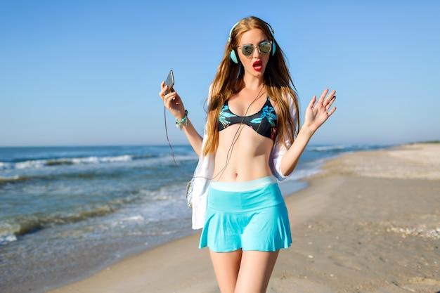 海岸を歩いて歌うスポーティな青いスカートのスリムな女の子。スマートフォンを押しながら夏の朝に海の景色を楽しんでいるサングラスの長髪の女性の屋外のポートレート。