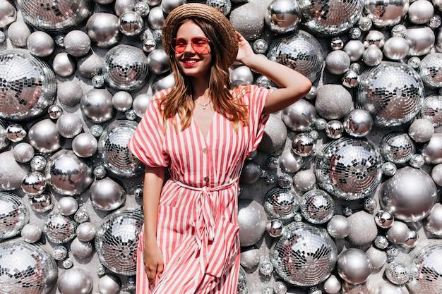Худенькая девушка в полосатом платье позирует с закрытыми глазами перед диско-шарами. открытый портрет веселой женской модели в соломенной шляпе стоя
