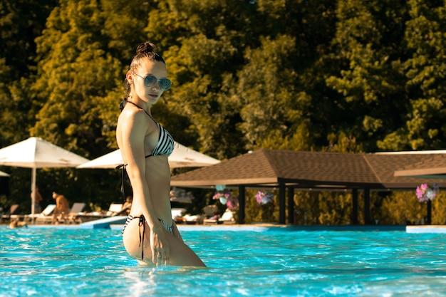 Худенькая девушка в солнцезащитных очках у бассейна
