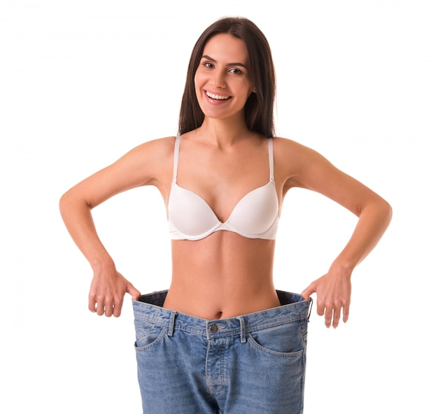 Slim girl is pulling her jeans and showing weight loss.
