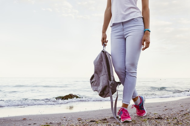 Slim girl in jeans and sneakers, walking along the beach in the evening with a backpack