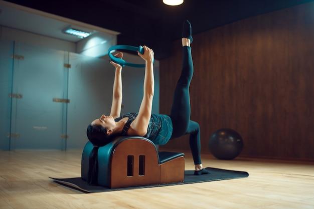 ジムでのピラティストレーニングのスリムな女の子、柔軟性