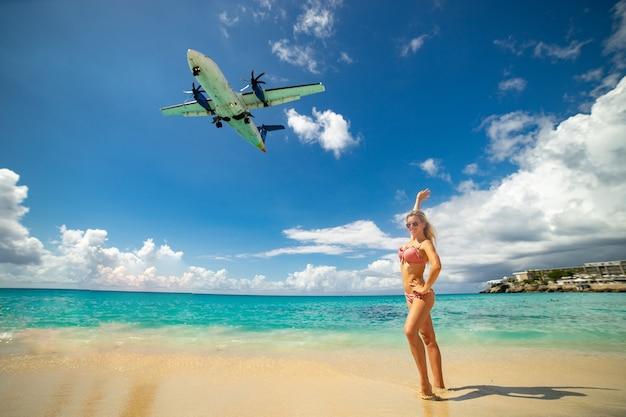 Maho 해변에서 거대한 비행기로 수영복을 입고 해변에서 포즈를 취하는 슬림 소녀. 휴가 및 happines의 개념