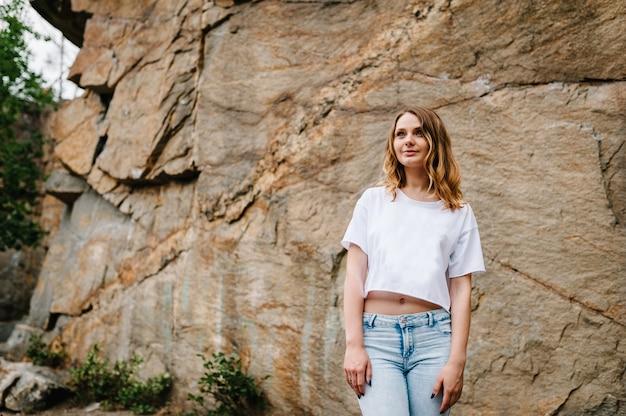 スリムな女の子が立ち、崖でポーズします。ジーンズと白いtシャツの女性の肖像画