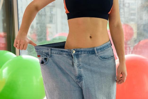 Slim girl wearing oversized pants in gym