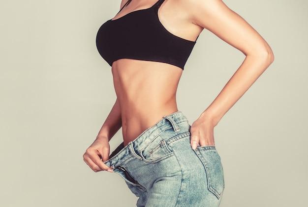 특대 바지를 입고 슬림 소녀입니다. 여자는 체중 감소를 보여줍니다. 다이어트. 스포츠 훈련, 건강한 식생활 후 날씬한 몸을 보여주는 여자. 체중 감량 개념입니다. 큰 바지를 입은 얇은 여성, 체중 감량 개념.