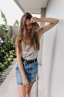スリムな女の子は恥ずかしがり屋の笑顔でポーズをとってエレガントなスカートを着ています。白い壁の近くに立っている長い髪の魅力的な女性の屋外の肖像画。