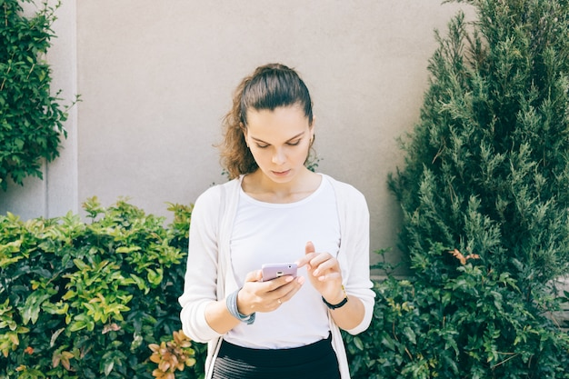 Slim girl in white cardigan using a mobile phone outdoors