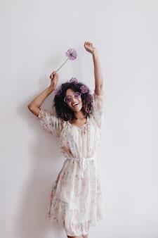 Худенькая девушка с черными волнистыми волосами танцует дома и улыбается. охлаждающая африканская молодая женщина в романтическом платье позирует с цветами.