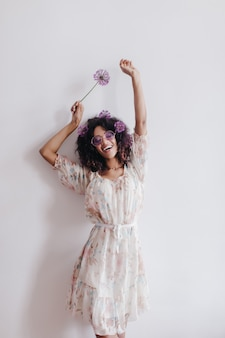Slim girl with black wavy hair dancing at home and smiling. chilling african young woman in romantic dress posing with flowers.
