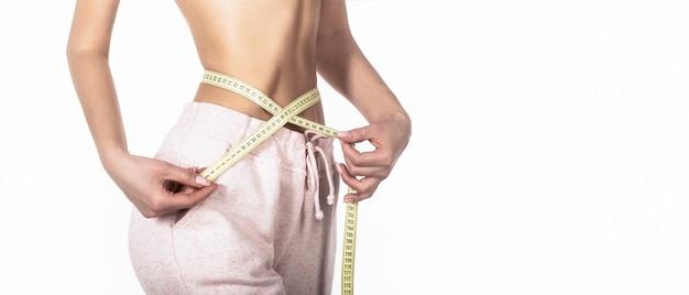 センチメートルのスリムな女の子。テープで彼女の腰を測定するクローズアップの女性。スリムな女性の体。巻尺を持つ女性。減量の概念。