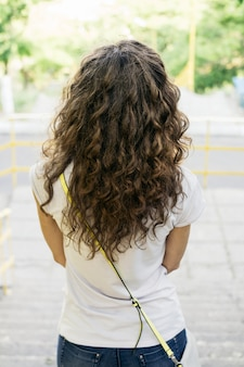 Slim girl with curly hair in a t-shirt and jeans on a walk