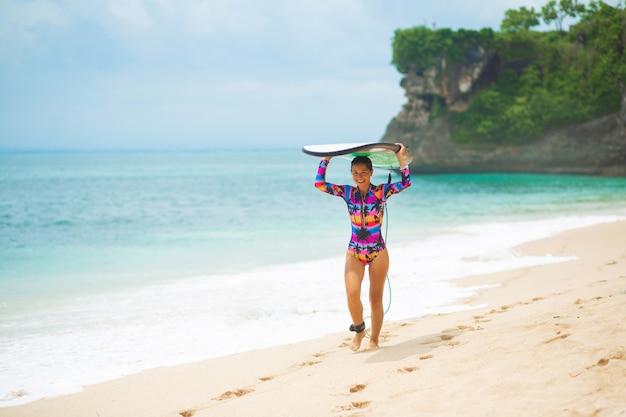 Худенькая девушка с доской для серфинга на тропическом песчаном пляже. здоровый активный образ жизни в летнем отдыхе.