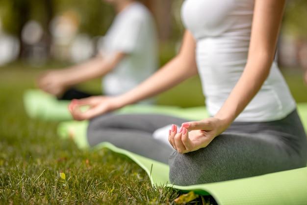 Худенькие девушки сидят в позах лотоса и занимаются йогой на ковриках для йоги на зеленой траве в парке в теплый день.