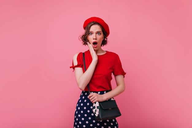 ショックを受けた感情を表現するウェーブのかかった髪型のスリムで魅力的な女性。ベレー帽のフランスの女性モデルの屋内写真。