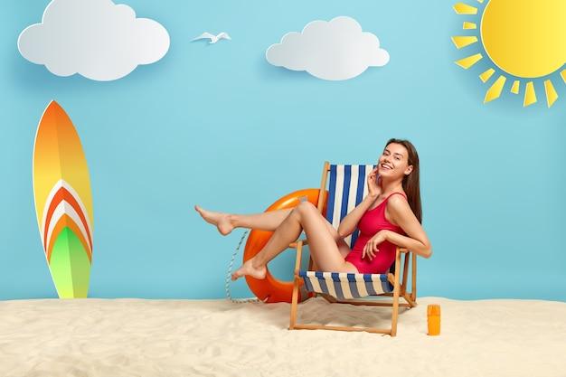 La bella donna esile riposa sulla sdraio in spiaggia, mostra le gambe snelle, indossa un bikini rosso, ha un aspetto felice