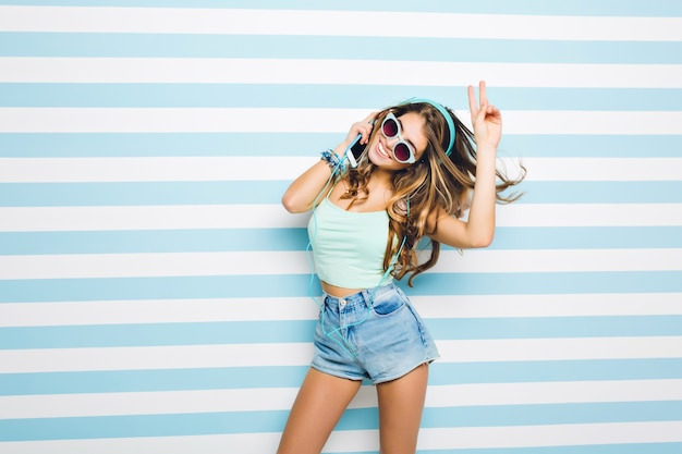 Slim good-looking girl wearing trendy sunglasses gladly posing with peace sign standing on striped wall. portrait of tanned long-haired young lady listening music in earphones and waving hands.