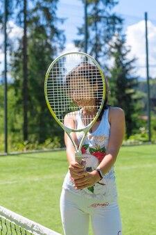 明るい夏の日にコートでテニスをする準備ができているスリムでゴージャスな女の子。