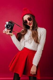 Slim donna splendida in cappello rosso e gonna in posa con la macchina fotografica