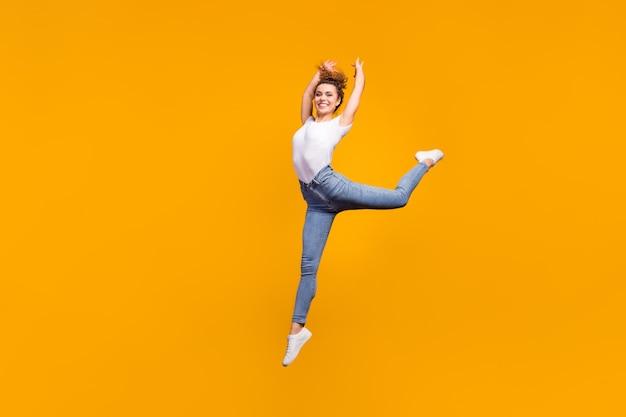 Стройная изящная жизнерадостная девушка прыгает танцует
