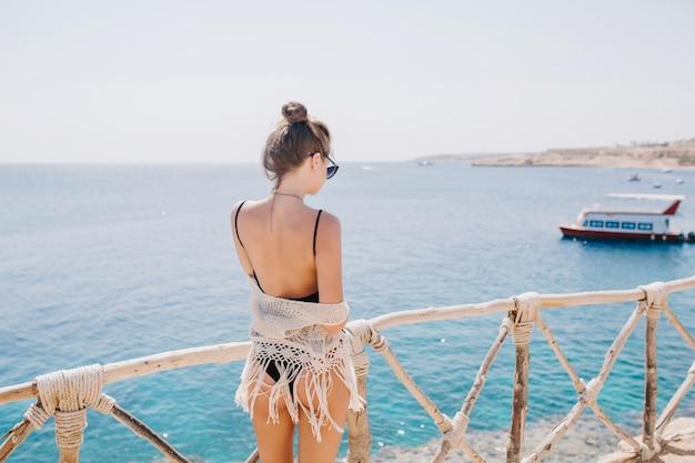 海の景色を楽しみ、打ち上げを見ているトレンディなヘアスタイルのスリムで優雅な女の子。海の上に立っている黒い水着で素晴らしい若い女性の後ろからの肖像画