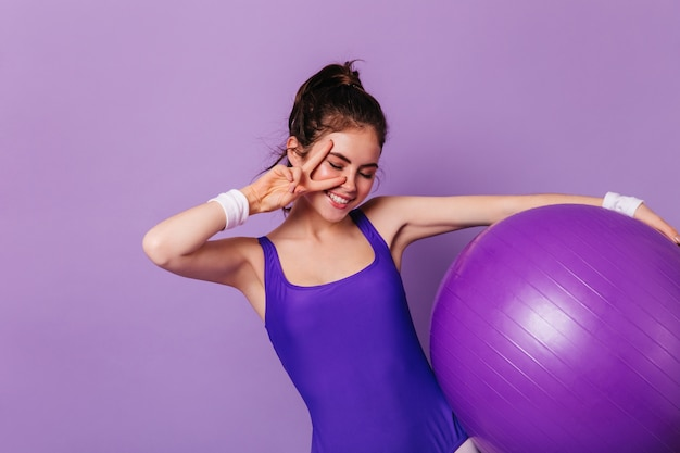Slim gymnast woman holds fitball and shows peace sign on purple wall