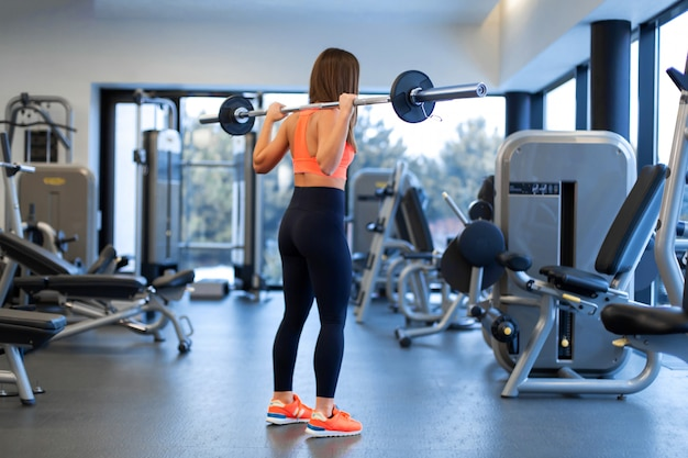 Slim handsome young woman in sportswear squats with a barbell on the shoulder in the gym