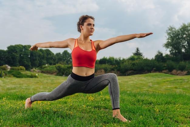 Стройная здоровая женщина чувствует себя просто потрясающе, занимаясь спортом на открытом воздухе в летний день