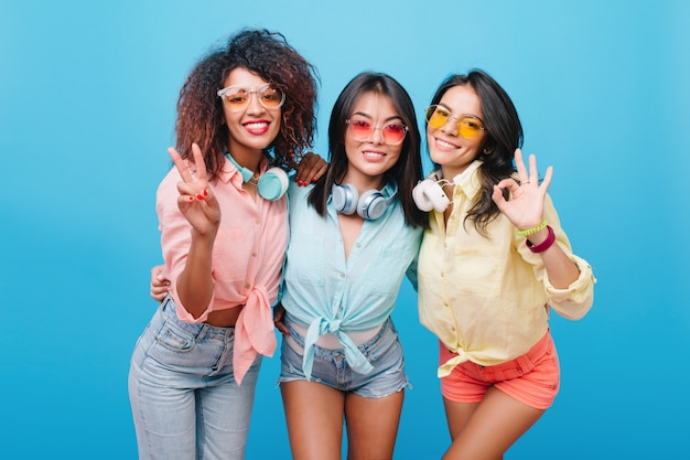 Slim hispanic girl in pink shorts posing with pleasure during party with female colleagues. indoor portrait of three stunning ladies in summer outfit dancing.