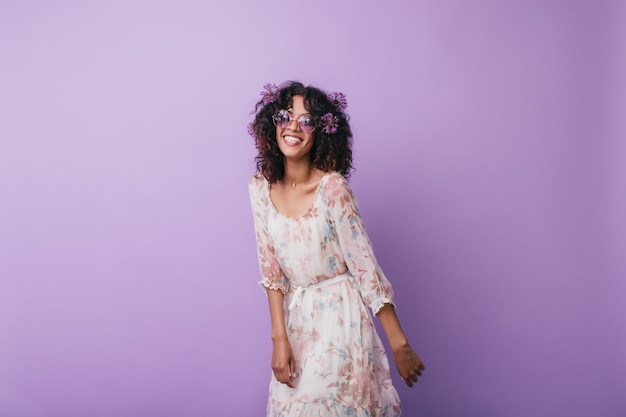 Slim inspired african girl laughing. indoor photo of enthusiastic curly young woman posing with alliums in hair.