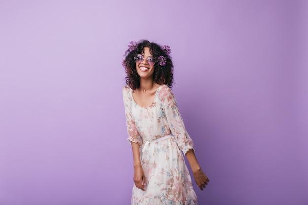 スリムなインスピレーションを得たアフリカの女の子が笑っています。熱狂的な巻き毛の若い女性の屋内写真。