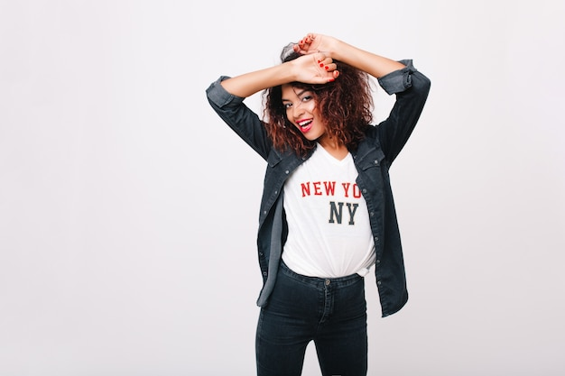 Slim inspired girl in denim pants pretty dancing and laughing. happy black young woman with red manicure posing with hands up having fun.