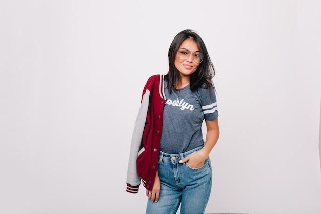 ポケットに手を入れて笑顔でポーズをとるグレーのtシャツとデニムパンツのスリムで楽しい女の子。ジーンズと爆撃機が立っている黒髪の女性モデル。