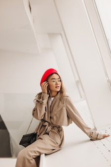 Slim lady in elegant beige trench coat and red beret touches her hair and sits by window on white wall