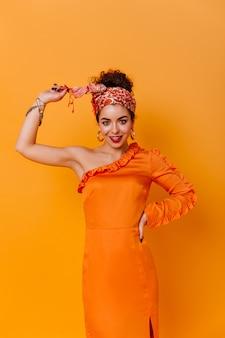 우아한 주황색 드레스와 아프리카 스타일의 머리띠를 입은 슬림 여성이 주황색 공간에 대해 달콤하게 미소 짓습니다.