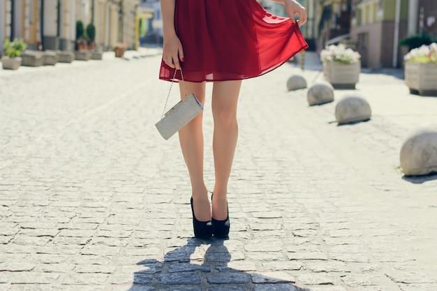 Стройная дама в модной одежде с днем рождения. на ней элегантное красивое платье, черные туфли на каблуках и сумка в руках. крупным планом, обрезанное фото