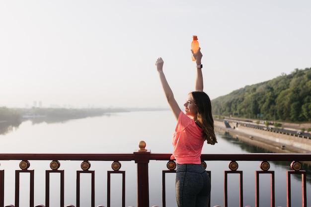 인생을 즐기는 스포츠 유니폼에 슬림 아가씨. 훈련 후 하늘을보고 유럽 여자 뒤에서 초상화.