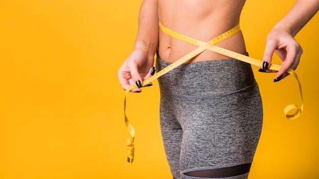 Стройная дама в спортивной одежде измеряет талию лентой