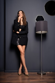 Slim lady in mini skirt and oversized black jacket standing near floor lamp in the room