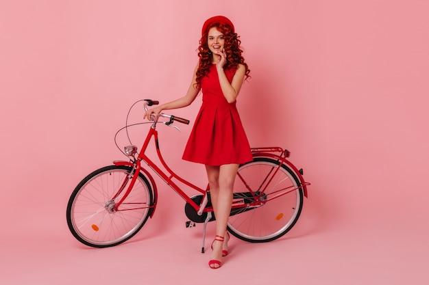 Slim signora in elegante abito rosso e berretto francese sta guardando la fotocamera con un sorriso, appoggiandosi alla bicicletta sullo spazio rosa.