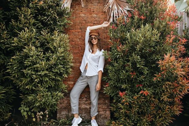 Signora snella in scarpe da ginnastica bianche, pantaloni grigi e camicetta bianca oversize posa contro un muro di mattoni circondato da cespugli.